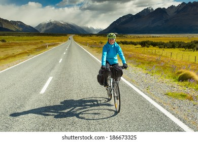 A mountain biker rides along a winding asphalt track in a valley among fields on a background of blue sky with clouds in New Zealand