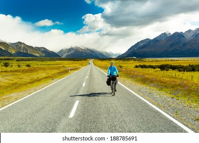 A mountain biker rides along a winding asphalt track in a valley among fields on a background of blue sky with clouds in New Zealand, Southern Alps