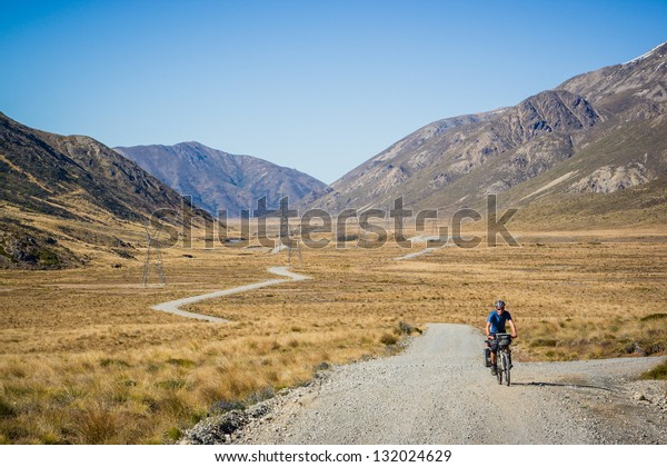 A mountain biker rides along a winding gravel track in a valley