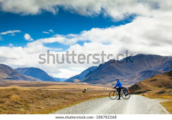 A mountain biker rides along a winding gravel track in a valley among fields on a background of blue sky with clouds. New Zealand, Southern Alps.