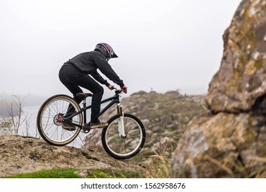Mountain biker rides a bicycle on the rocks, extreme sport. Downhill,