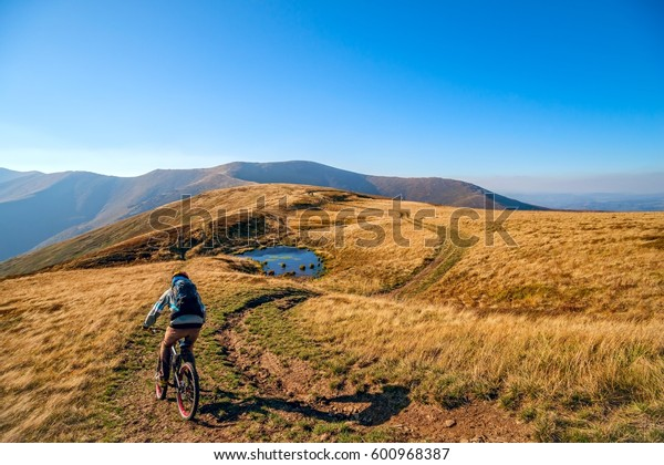Mountain biker riding the mountain bike on the trail to horizon line against beautiful fall mountain landscape.  Extreme sport concept.