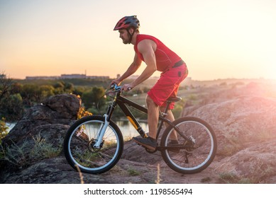 Mountain biker riding down the cliff, free space. Active lifestyle, bike ride.