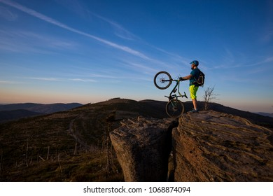 Mountain biker riding on bike in summer mountains forest landscape. Man cycling MTB. Outdoor sport activity.