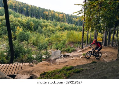 Mountain biker riding on bike in autumn inspirational mountains landscape. Man cycling MTB on enduro trail track. Sport fitness motivation and inspiration.