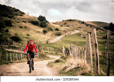 Mountain biker riding on bike in summer mountains landscape. Man cycling MTB on rural country road. Sport fitness motivation and inspiration.