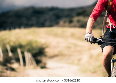 Mountain biker riding on bike singletrack trail in autumn mountains. Man rider cycling MTB on country road or single track. Sport fitness motivation, inspiration in beautiful inspirational landscape.