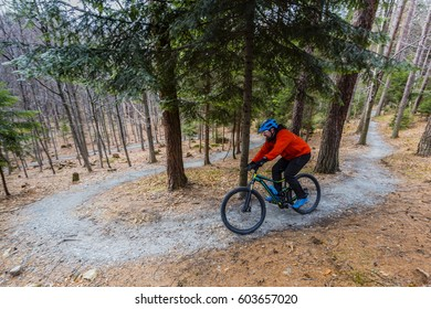 Mountain biker riding on bike in early spring mountains forest landscape. Man cycling MTB enduro flow trail track. Outdoor sport activity.