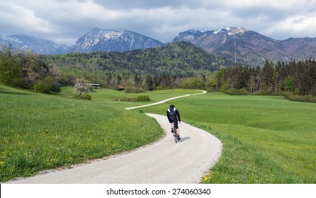 Mountain biker, riding on a scenic winding road in alpine region on typical April day with cloudy sky, last snow in the mountains and blooming cherry tree. Location: Stefanja gora, Krvavec, Slovenia.