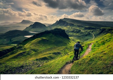 Mountain biker riding through rough mountain landscape of Quiraing, Isle of Skye, Scotland, UK