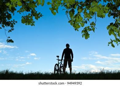Mountain biker silhouette in summer nature
