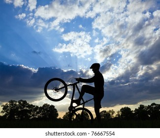 Mountain biker silhouette in summer over blue cloudy sky
