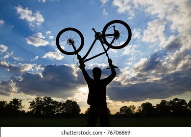 Mountain biker silhouette in summer over blue sunset sky, cycling and success concept