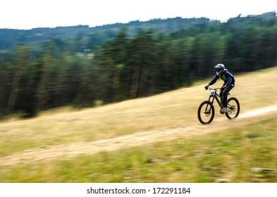 Mountain biker speeding down the hill. Panning shot