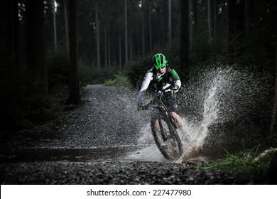 Mountain biker speeding through forest stream. Water splash in freeze motion.
