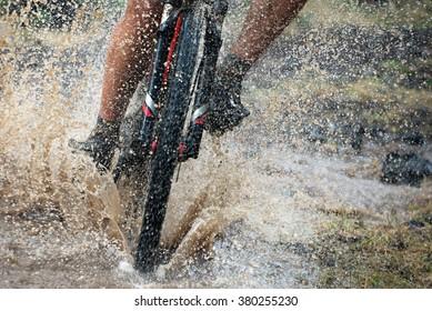 Mountain biker speeding through forest stream. Water splash.