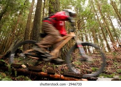 A mountain biker speeds over a wooden bridge.