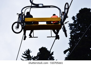 Mountain bikers on a chair lift in the mountain.