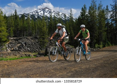 Mountain bikers traveling a dirt road under Mount Bachelor Bend, Oregon, United States - June 21, 2007 with model releases