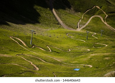 Mountain bikers using the chairlift in the Bike Park at Les Deux Alpes in the French Alps. A narrow twisty trail runs underneath.