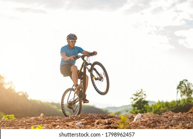 Mountain bikes cyclist cycling, Asian man athlete riding biking jumping on rocky terrain trail, extreme sport wear gear uniform helmet, exciting freedom outdoor sunset nature healthy active lifestyle