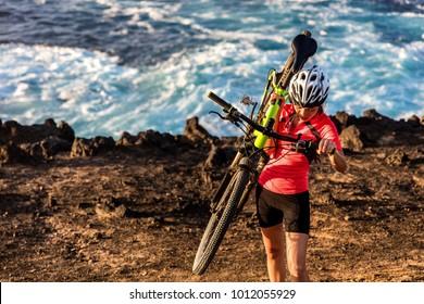 Mountain biking carrying bike uphill walking up hill. MTB biker cyclist riding outdoors. Cycling sports.