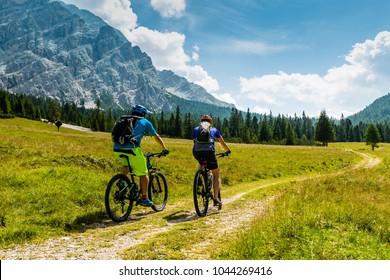 Mountain biking couple with bikes on track, Cortina d'Ampezzo, Dolomites, Italy