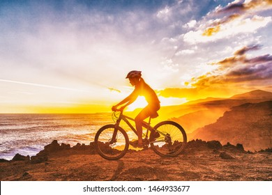 Mountain biking cyclist girl riding MTB bike on coast trail against sunset. Silhouetter of woman doing sports outdoors. Healthy and Active lifestyle.
