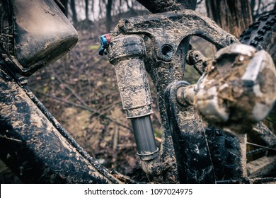 Mountain biking, dirty and broken bicycle closeup. MTB bicycle with mud and sand waiting for cleaning and repairing. Adventure and extreme enduro cycling sport concept.