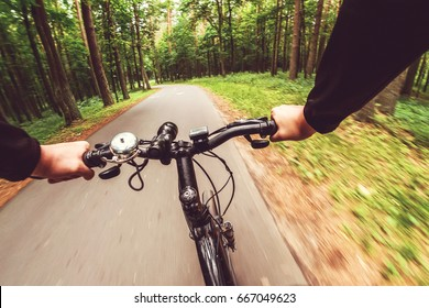 Mountain biking down hill descending fast. View from bikers eyes. Motion blurred