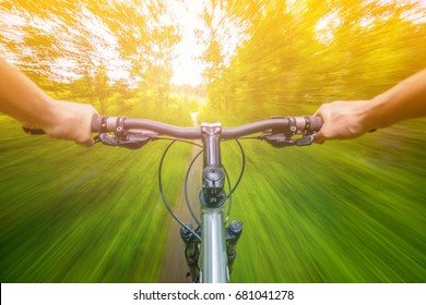 Mountain biking down hill descending fast on bicycle with motion blur. View from bikers eyes.
