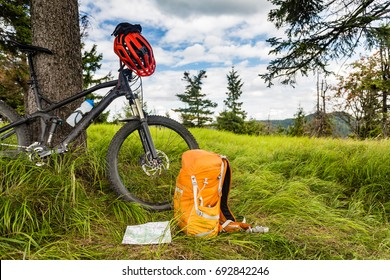 Mountain biking equipment in the woods, bikepacking adventure trip in green mountains. Travel campsite and MTB cycling with backpack, wilderness forest in Poland.