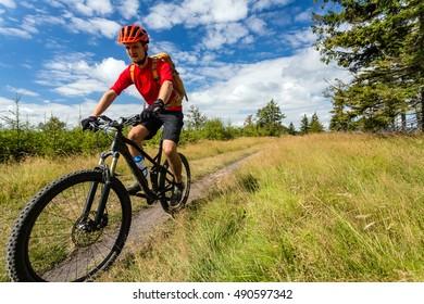 Mountain biking man riding on bike in summer inspirational mountains landscape. Rider cycling MTB on enduro trail path. Sport fitness motivation and inspiration. Rider mountain biker in summer woods.