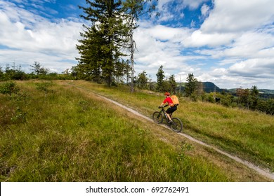 Mountain biking man riding on bike in summer inspiring mountains landscape. Rider cycling MTB on enduro trail path. Sport fitness motivation and inspiration in summer woods.