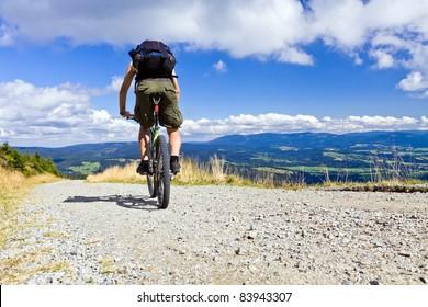 Mountain biking in summer mountains, man riding a bike in summer nature