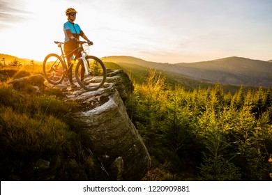 Mountain biking woman riding on bike in autumn mountains forest landscape. Woman cycling MTB flow trail track. Outdoor sport activity.