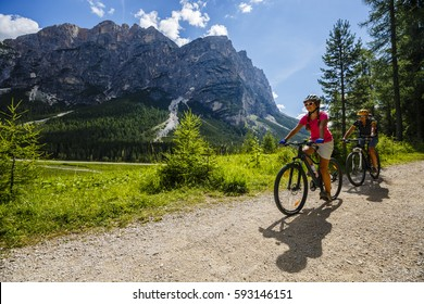 Mountain biking woman and young girl along river in Dolomites, Italy