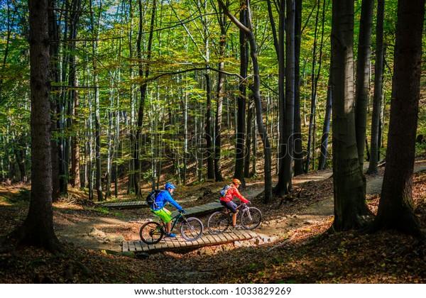 Des femmes en VTT et des hommes faisant du vélo au coucher du soleil dans le paysage forestier des montagnes. Couple cyclisme sur la piste de piste d'enduro MTB. L'activité sportive en plein air.