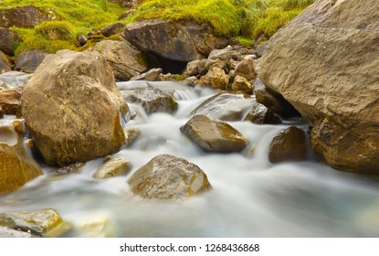 Mountain brook with flowing water among big stones, long exposition