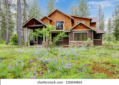 Mountain cabin home wood exterior with forest and flowers.