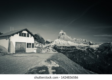 mountain cabin refuge beside tre cime di lavaredo in dolomites mountain range in sunny snowy winter in black and white