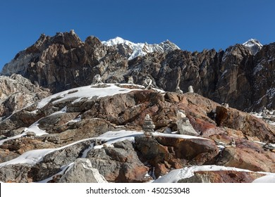 Mountain cairns on Everest Base Camp route in Himalayas, Nepal. Beautiful landscape with cairn markings on the big rock partly covered with snow - concept for hiking, climbing, and outdoor adventures.