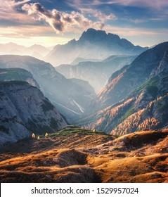 Berglauf, beleuchtet durch helle Sonnenliegen bei Sonnenuntergang im Herbst in Dolomiten, Italien. Landschaft mit Bergrücken, Felsen, bunten Bäumen und orangefarbenem Gras, Almen, goldenes Sonnenlicht im Herbst. Alpen