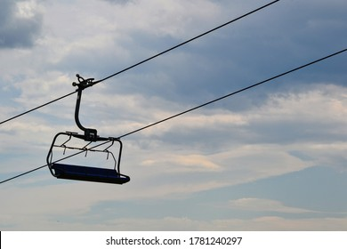 Mountain chairlift. 4-seater chairlift. The ski lift going tothe station. Close up of an empty four person chair lift hanging at a ski lift wires