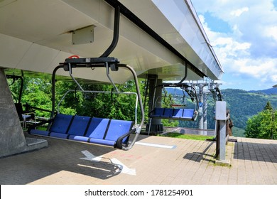 Mountain chairlift. Blue 4-seater chairlift. The ski lift reaches the station. Summer view. Close up of an empty four person chair lift hanging at a ski lift top station