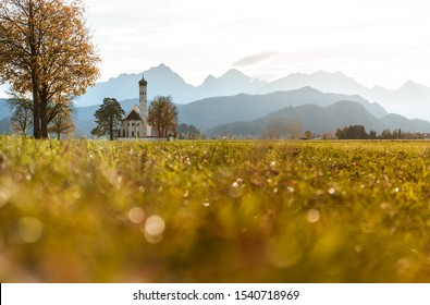 Mountain church with alp panorama background during golden hour sunset in green grass