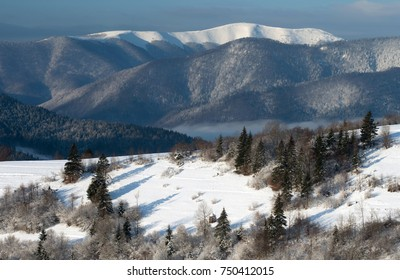 Mountain clearing in the snow against the backdrop of the mountain range, lit by the sun. Winter landscape.