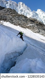 mountain climber crosses over a large and deep crevasse or bergschrund as he begins his climb of a steep north face of ice and snow in the Alps