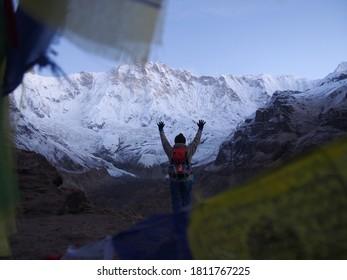 A mountain climber gaze across Talcho (Tibetan praying flags) at the snow-covered mountains in the early morning, ABC (Annapurna Base Camp) Trek, Annapurna, Nepal