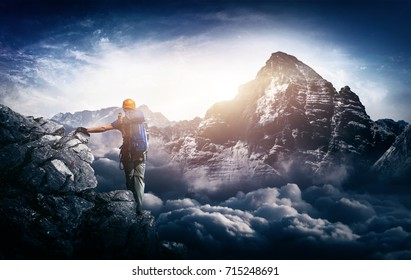 A mountain climber with a majestic sunrise view over towering snow capped mountains and cloud tops.